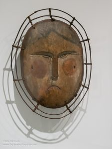 Carved and painted wooden mask of a woman's face
